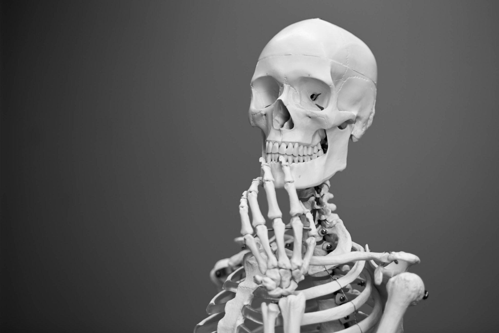 Tipps für Zeitmanagement, mehr Fokus und Klarheit: Ein Skelett in nachdenklicher Pose